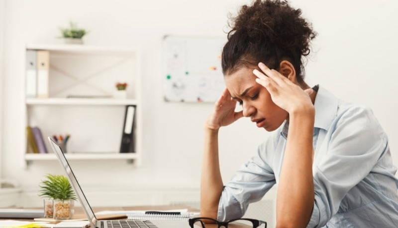 Stressed woman holder her head with her elbows resting on her desk
