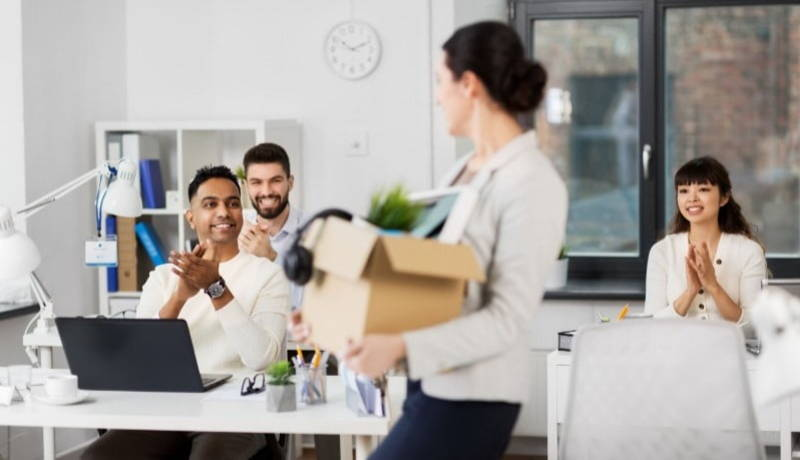 Woman carrying cardboard box through office while employees applaud